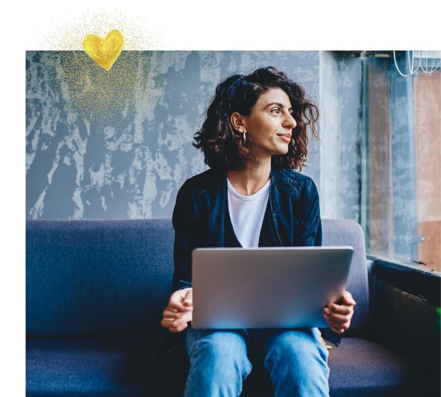 Frau mit Laptop auf dem Schoß schaut glücklich aus dem Fenster